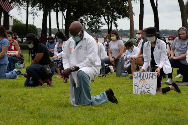 UF Health Jacksonville physicians socially distanced and kneeling in silence with other area health care providers and community residents in Jacksonville Memorial Park as part of the #WhiteCoatsforBlackLives initiative
