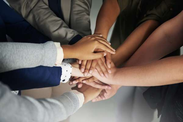 Closeup shot of a group of unrecognisable businesspeople joining their hands together in unity